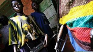 रवांडा के सैनिकों की मौजूदगी की जानकारी जुटाने के लिए कॉन्गो गणराज्य में संयुक्त राष्ट्र के अभियान के दौरान वलीकेल ज़िले के एक गाँव में चार दिसंबर 2004 के दिन संयुक्त राष्ट्र के शांति रक्षक के पास खड़ा एक बाल सैनिक.