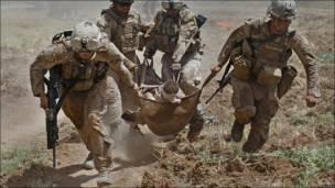 Группа американских морских пехотинцев несет к вертолету бойца, раненого при взрыве самодельного взрывного устройства в провинции Гельменд