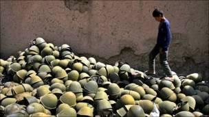 Афганский мальчик запечатлен на горе старых советских касок,  оставшихся в Афганистане еще со времен, когда здесь действовал военный контингент СССР