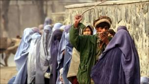 Афганец использует палку, чтобы поддержать порядок в очереди за гуманитарной помощью в Кабуле