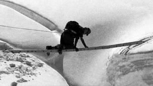 Альпинист перебирается через пропасть
