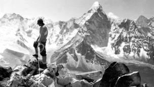 Альпинист на верхушке скалы в Гималаях.