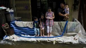 Дети смотрят на разлившиеся воды реки Чао Фрайя