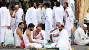 د سوریې حاجیان په مکه مکرمه کې مسجد الحرام ته نژدې د سړک پرغاړه خواړه خوري.