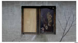 Цыганская девочка выглядывает из окна
