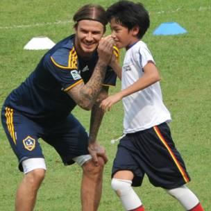 """ديفيد بيكهام يداعب صبيا خلال جولة تدريبية في جاكارتا ضمن زيارة فريق ناديه """"لوس انجيلز غالاكسي"""" إلى اندونيسيا"""