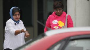 Supir taksi Asnima Aminudin membuka pintu untuk penumpangnya