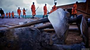Detendtos do presídio de Nsida carregam pás para trabalhar. Foto: Graham Holliday