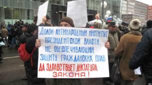 Мужчина с плакатом, требующим отказа от президентской власти