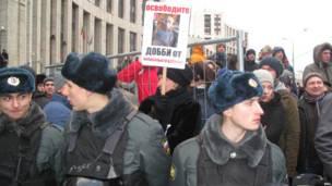 Женщина с плакатом и полицейские на митинге в Москве