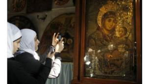 دوه فلسطيني مسلمانې د بیت لحم په المهد کلیسا کې د کښل شویو انځورونو عکسونه اخلي.