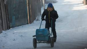 蒙古首都烏蘭巴托某村莊一名男孩推著載有水罐的手推車
