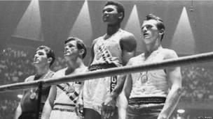 Кассиус Клей (он же Мохаммед Али) на пьедестале почета на Олимпийских играх в Риме