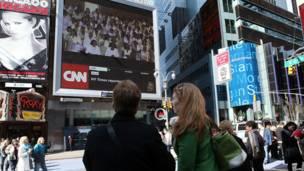 Peatones se detienen a mirar la transmisión del velorio en Times Square
