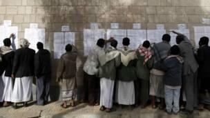 يمنيون يراجعون قوائم الناخبين في مركز اقتراع في حي الحصبة بصنعاء
