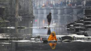 a devotee meditating submerged in Bagmati river