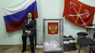 Một sỹ quan cảnh sát ngồi cạnh thùng phiếu tại St. Petersburg