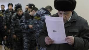 Một cử tri đang đọc thông tin trên phiếu bầu trong khi các sỹ quan cảnh sát đặc nhiệm chuẩn bị bỏ phiếu ở Moscow