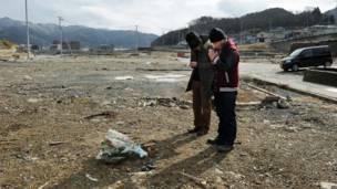 Một người cha cùng con trai cầu nguyện cho người thân bị mất tích ở Onagawa, tỉnh Myagi