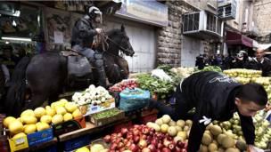 Палестинский подросток влез на ящики с фруктами, убегая от конного израильского полицейского.