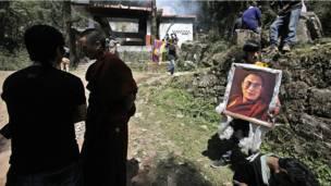 Тибетец держит портрет духовного лидера Далай-ламы, во время кремации Джамфела Йеши.