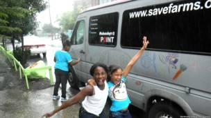 Niños frente a la camioneta de la  Sociedad por los Valores y la Educación sobre Acuaponia