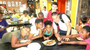 Niños en The Point a punto de comer una tilapia