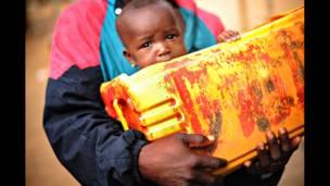 В руках родителя - ребенок и грязная канистра