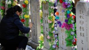 Wata mata tana tusa rubutun da ke kabarin kakanninta a wata makabarta a Beijing, China, ranar 4 ga watan Afrilun 2012