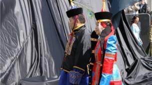 Люди в национальных костюмах у подножия памятника.