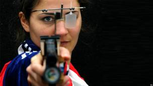 A Paralympics athlete takes aim with her gun