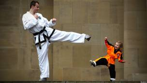 Man and girl in Tae Kwon Do uniforms pose for a photo