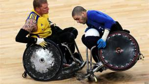 Two wheelchair rugby players collide during a match