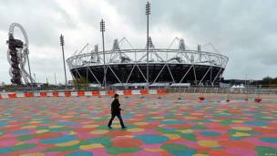 A woman walks past the Olympic stadium