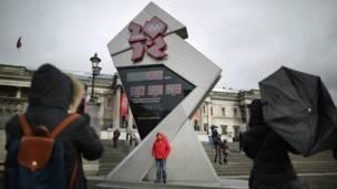 د لندن په تلفارګر سیمه کې د اولمپیک لپاره سرچپه ساعت لګول شوی، چې ګڼ سیلانیان یې ترڅنګ یادګاري عکسونه اخلي.