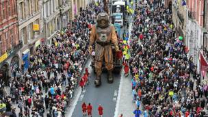 A giant puppet is carried along a street filled with spectators
