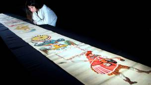 A researcher looks at an illustrated ancient scroll