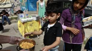 Дети в Афинах стоят в очереди за едой к уличной кухне