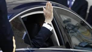 Олланд приветствует собравшихся из окна машины