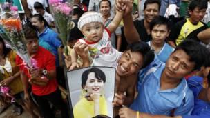Miến Kiều ở Mahachai cầm ảnh chân dung của bà Suu Kyi để chào đón bà