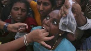 امرأة هندية تتلقى علاجا بالاسماك في حيدر اباد، حيث تشهد المدينة توافد الآلاف في شهر يونيو من كل عام لتلقي علاج لحساسية الصدر