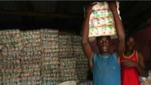 Мужчины несут соль в одном из магазинов города Бунагана.