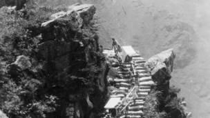 Personas subiendo por una escalera empinada