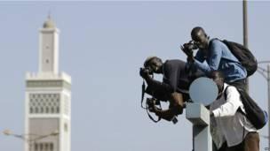 Des photo-journalistes juchés sur un abri-bus lors d'une manifestation à Dakar. 23.04 2013