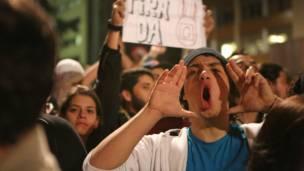 Участник демонстрации кричит
