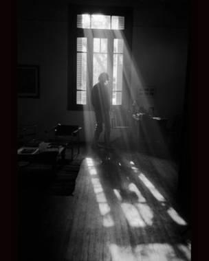 Hombre contra ventana, sombras y reflejos