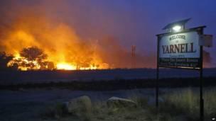 Пожар горит у вывески о въезде в город Ярнелл