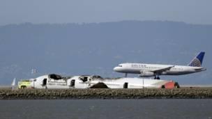 Pesawat United Airlanes mendarat di dekat bangkai pesawat Asiana