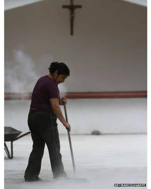 ज्वालामुखी की राख को साफ़ करती एक कर्मचारी.