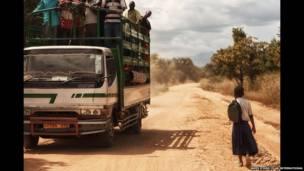 Caminhão passa por Sylvia na estrada. James Stone/Plan International
